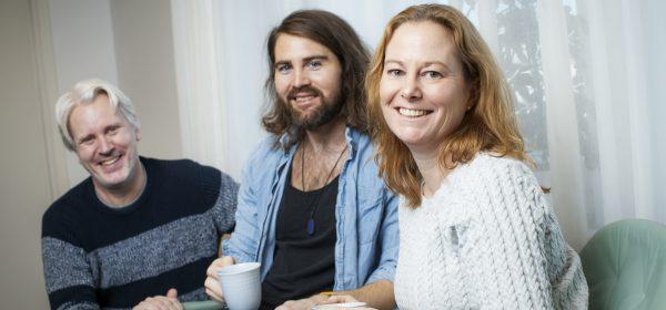 Tre personer, två män och en kvinna, sitter bredvid varann och tittar leende in i kameran.