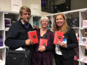 Tre personer poserar bredvid varandra med boken Vändpunkter i handen.