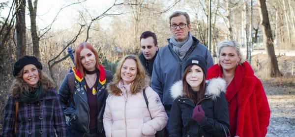 En grupp på sju personer i olika åldrar poserar tillsammans utomhus i ett lite vintrigt landskap.