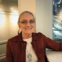 Närbild av en leende kvinna i rödbrun jacka.
