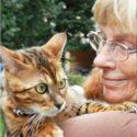 Kvinna med en katt i famnen. Hon ser kärleksfullt på katten.