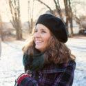Kvinna i halvlångt brunt hår med svart basker står utomhus i en park.