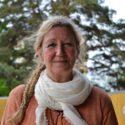 Kvinna med långt hår i en fläta och en vit sjal runt halsen.